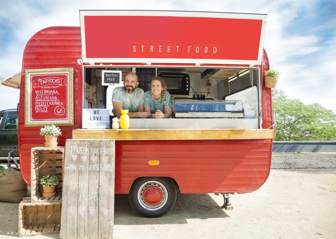 A concept of Local SEO: Red food truck and the young couple who own and run it